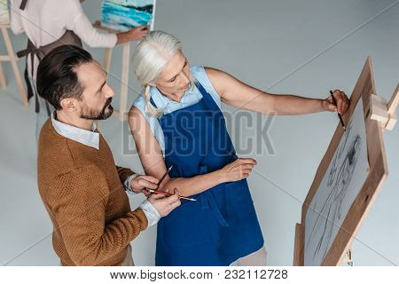 High Angle View Of Mature Man Holding Pencils And Looking At Senior Woman Drawing On Easel