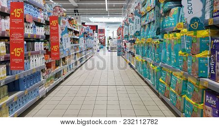 Piatra Neamt, Romania - March 16: Shopping Cart In Supermarket Aisle With Diaper Shelves In Shopping