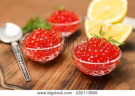 Bowls with delicious red caviar on wooden board, closeup