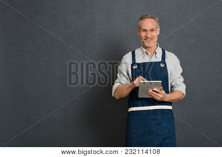 Smiling man using digital tablet for his business isolated on grey background. Portrait of happy mature man in blue apron. Satisfied business owner take orders on digital tablet and looking at camera.