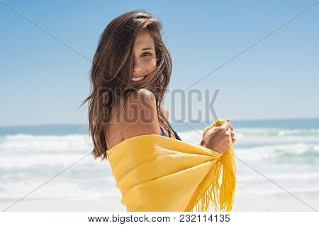 Cheerful young woman in yellow sarong at beach. Happy smiling girl enjoying the beach and looking at camera. Latin tanned woman feeling refreshed in yellow scarf during summer vacation.