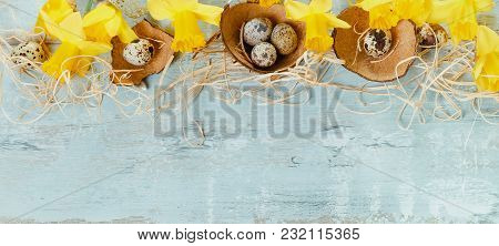 Spring Floral Border, Beautiful Fresh Daffodils Flowers And Easter Eggs On Blue Wooden Desk. Easter