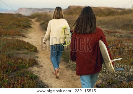 Two female surfers walking near the coastline with surfboards
