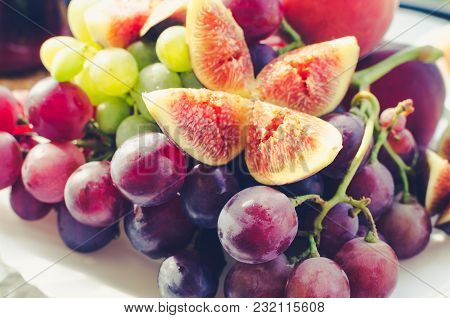 Plate With Mixed Fruits: White And Burgundy Grapes, Figs And Peach.