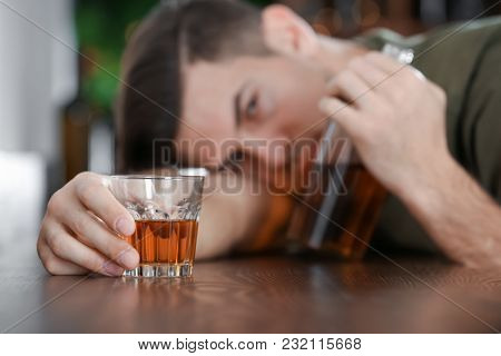 Young man with glass and bottle of drink in bar. Alcoholism problem