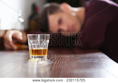 Drunk man with glass of drink in bar. Alcoholism problem