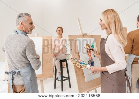 Senior Artists Painting And Looking At Each Other In Art Studio