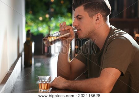 Young man drinking alcohol from bottle in bar