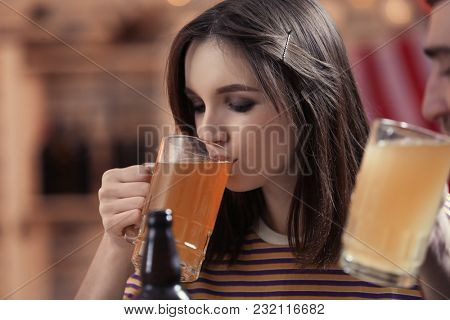 Woman drinking beer in sport bar