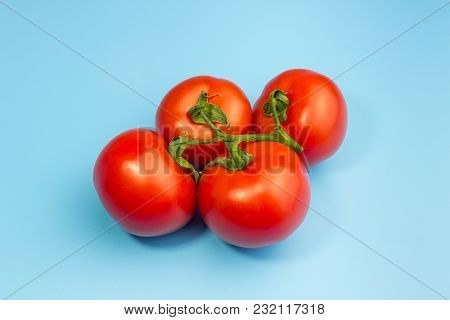 A Branch Of Red Ripe Tomatoes On A Soft Blue Background
