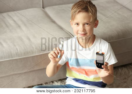 Little diabetic boy with digital glucometer and lancet pen at home