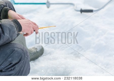Winter Fishing. A Tool For Winter Fishing In Hands. A Fishing Rod In The Hands For Freezing.
