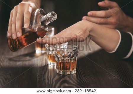 Woman refusing to drink alcohol in bar