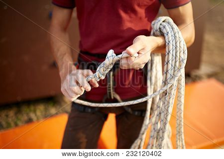 A Rock Climber Tie A Knot On A Rope. A Person Is Preparing For The Ascent. The Child Learns To Tie A
