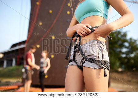 Isolated View Of Caucasian Woman Putting On Belaying Harness For Practice On Artificial Rock Wall Ou