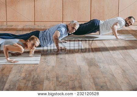 Female Instructor Exercising With Mature Men On Yoga Mats At Training Class
