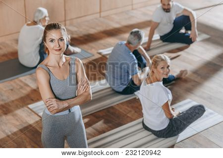 High Angle View Of Female Instructor Looking At Camera While Senior People Exercising On Yoga Mats