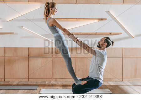 Middle Aged Couple Practicing Yoga Together At Training Class