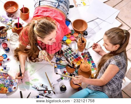 Authentic artist children girl paints with set palette watercolor paints palette and brush in morning sunlight. Painting in studio on floor. Relaxation creativity for solving psychological problems.