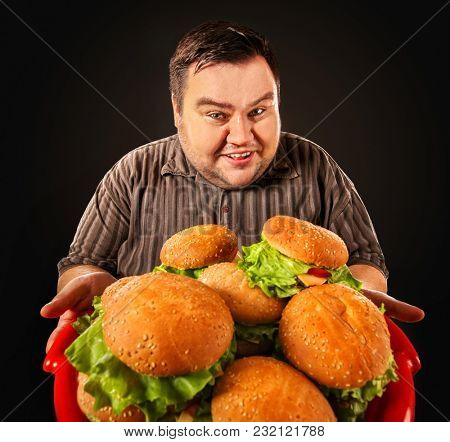 Man eating fast food hamberger. Fat person made great huge hamburger and admires him, intending to eat it. Junk meal leads to obesity. Feast on occasion of feast.