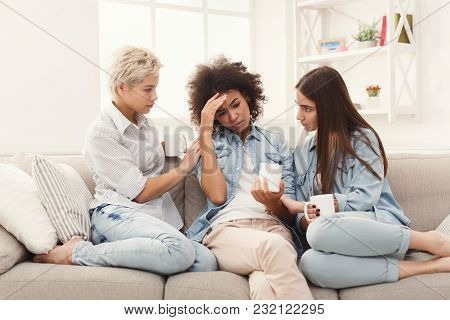 Young Women Talking And Consoling Their Sad Friend. Casual Girls Sharing Problems At Home. Unity And