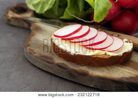 Bread With Butter And Radish On A Wooden Board.