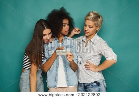 Three Female Friends With Smartphones At Blue Studio Background. Smiling Women Watching Videos On Mo