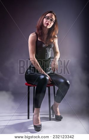 Sexy Young Woman In A Corset And Latex On A Chair.