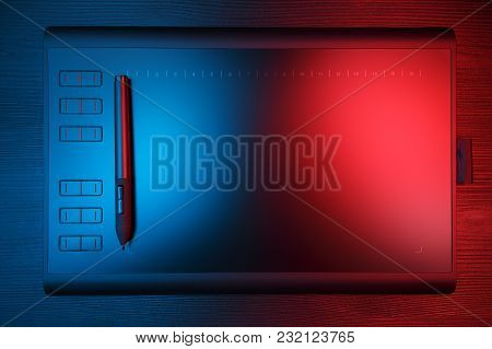 Graphic Tablet With Pen For Illustrators And Designers On Black Wooden Background