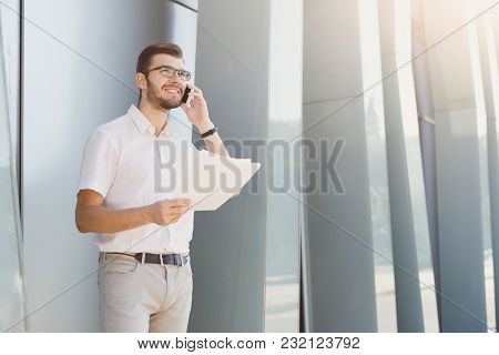 Handsome Happy Businessman Or Lawyer In Eyeglasses Is Talking On Cell Phone And Holding Documents In