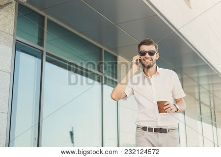 Young Happy Businessman In Sunglasses Talking On Cell Phone And Drinking Coffee While Walking Near M