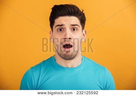 Close up portrait of an astonished young man in t-shirt looking at camera isolated over yellow background
