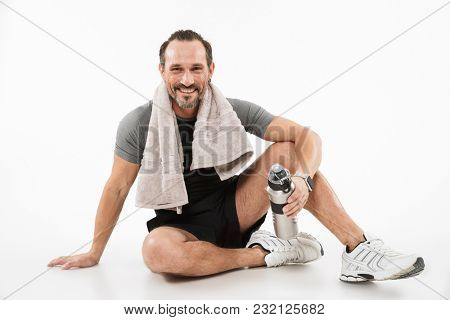 Portrait of a smiling mature sportsman drinking water while sitting on a floor and resting isolated over white background