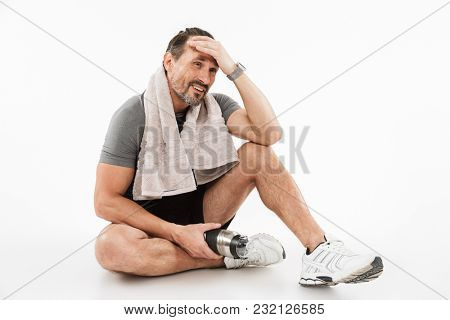 Image of laughing strong mature sportsman sitting with towel and water isolated over white background wall. Looking aside.