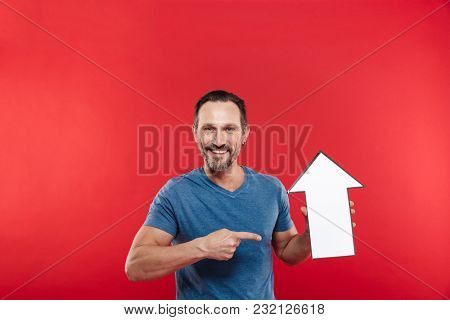 Good-looking brunette man holding blank speech arrow pointer directing upward on copy space isolated over red background