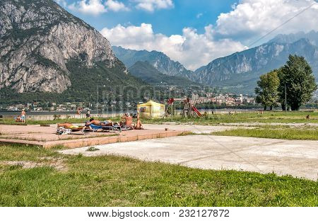 Malgrate, Lombardy, Italy - August 28, 2015: People Resting On The Lakefront Of Malgrate Located On