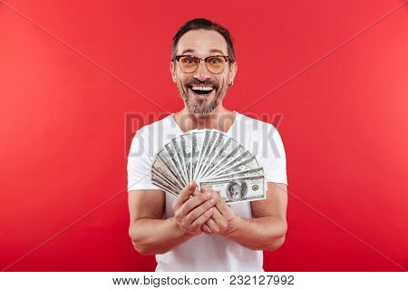 Photo of excited and rich man in casual white t-shirt smiling and demonstrating fan of money in dollar banknotes holding in hands isolated over red wall