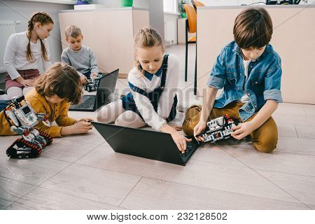 Kids Programming Robots With Laptops While Sitting On Floor, Stem Education Concept