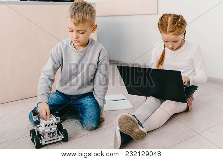 Focused Kids Sitting On Floor At Stem Education Class With Robot And Laptop