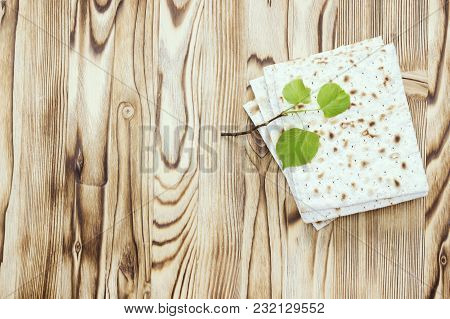 An Overhead Photo Of Matzah Or Matza Pieces And A Small Spring Fresh Linden Tree Branch. Matzah On T