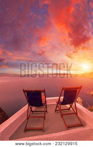 Sunbeds on Santorini's roofs at sunrise