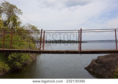A Rustic Suspension Bridge Over A Part Of Sorabora Lake In Central Sri Lanka With Wooded Hills And R