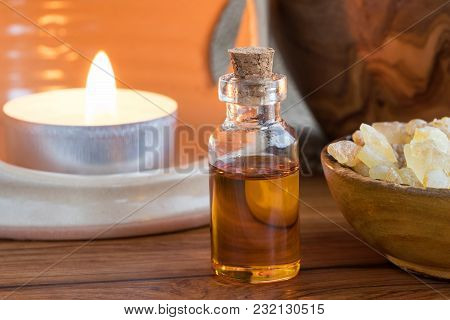A Bottle Of Frankincense Essential Oil With Frankincense Resin And A Candle