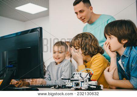 Teacher Programming Robot With His Teen Students