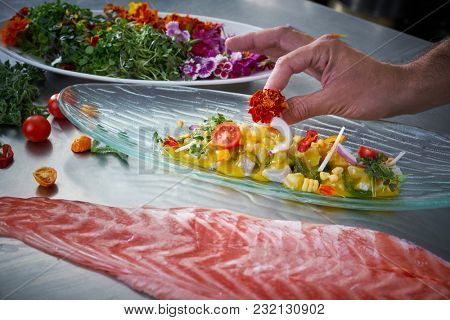 Chef hands garnishing flower in ceviche dish at stainless steel kitchen