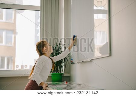 View Of Little Child Wiping Whiteboard With Sponge