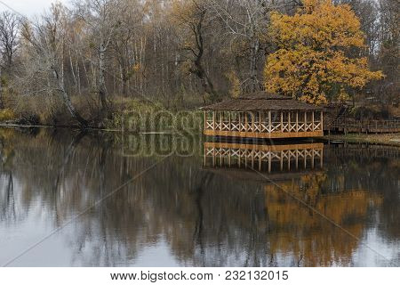 Wooden House On The River. Autumn Forest With Yellow Leaves