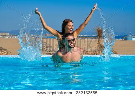Tourist couple piggyback in infinity pool on a beach resort splashing water
