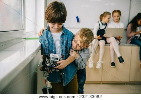 Little Kids With Diy Robot Embracing On Machinery Class