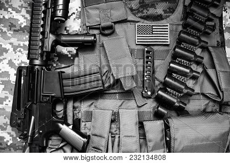 Upper view photo of a military tactacal bulletproof vest, cartrige belt and rifle laying on camouflage cloth background. poster